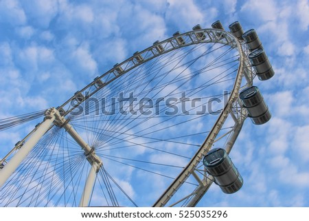 Big ferris wheel with cabins on blue sky, Singapore Flyer. #525035296