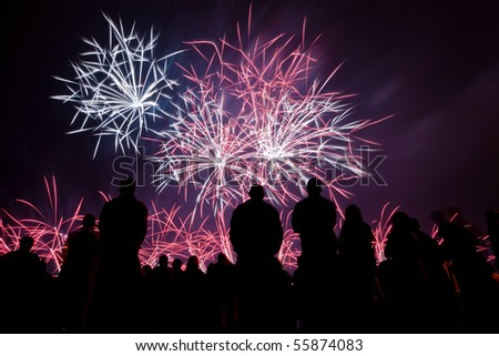 Big fireworks with silhouetted people in the foreground watching