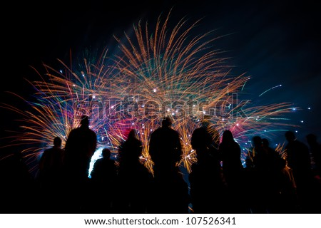 Big fireworks with silhouettes of people watching it