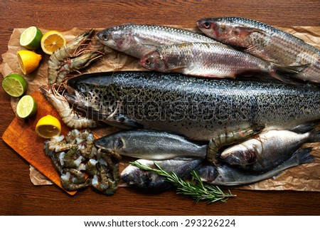 Big fish platter on the counter fish restaurant. Fresh shrimp and salmon carcass decomposed into brown parchment paper