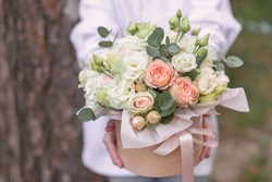Big flowers arrangement in a hat box was created by a florist for a wedding gift. White Freesia ,  eustoma flowers, roses and eucalyptus in a bouquet. Woman florist making a flowers bouquet