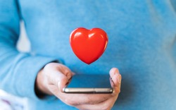 Big flying red heart. Mobile phone, smartphone in hand of man. Valentine's day holiday concept.Online love,remote communication on internet,social networks.Virtual dating,calls,technology.Coronavirus.