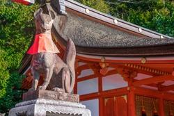 big fox stone statue on the stage inside Fushimi Inari Shrine (Fushimi Inari Taisha) Asian temple in Japan.