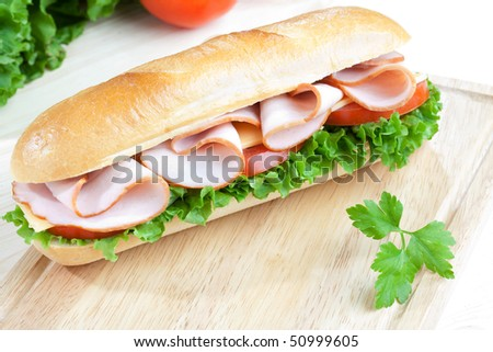Big fresh sandwich on wooden board with some veggies on the background
