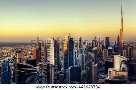 Big futuristic city at colorful sunset. Fantastic skyline of Dubai, UAE.