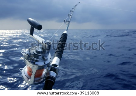 Big game boat fishing in deep sea on boat under cloudy winter time