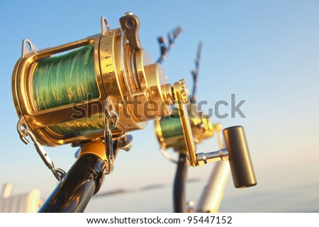 big game fishin reels and rods lit by setting sun