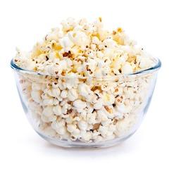 Big glass bowl of freshly popped popcorn isolated on white background