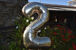 big golden balloon number 2 in the garden with flowers