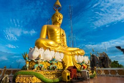 Big Golden Buddha statue against blue sky in Thailand temple