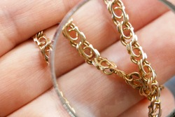 big golden chain in hands, pawnshop concept, jewerly shop concept, closeup