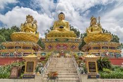 Big golden statues of Avalokiteshvara, Buddha Shakyamuni and Padmasambhava on lotus thrones in Buddha park, Swayambhunath area, Kathmandu, Nepal