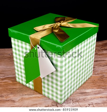 Big green gift box with golden ribbon on wooden table