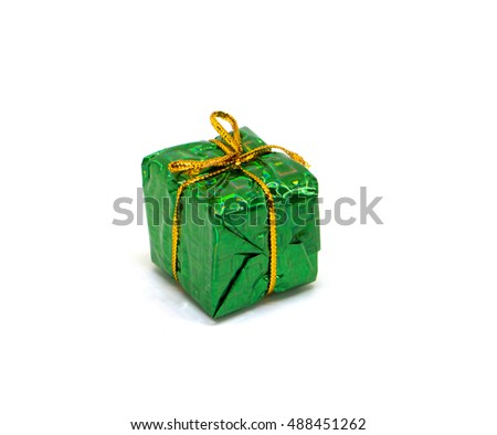 Big green gift on white background. Christmas gift box in foliage wrapping with gold thread bow. New year fir tree ornament. Winter holiday symbol isolated. Christmas present image for season decor