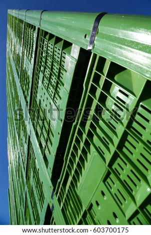 Big green plastic crates for fruits are stacked and waiting with desire to be filled with fresh fruits. Yes, and it looks like buildings in a city #603700175