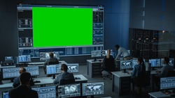 Big Green Screen Horizontal Mock Up in a Mission Control Center Room with Flight Director and Other Controllers Working on Computers. Team of Engineers Work in Monitoring Room Full of Displays.