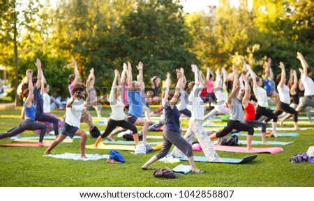 big group of adults attending a yoga class outside in park - Shutterstock ID 1042858807