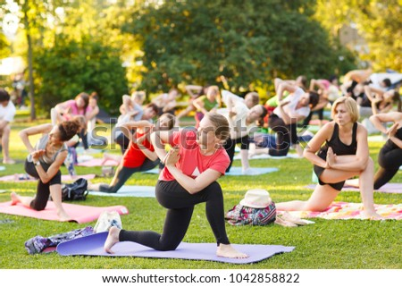big group of adults attending a yoga class outside in park - Shutterstock ID 1042858822