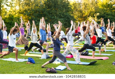 big group of adults attending a yoga class outside in park - Shutterstock ID 1042858831