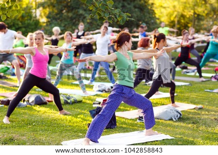 big group of adults attending a yoga class outside in park - Shutterstock ID 1042858843