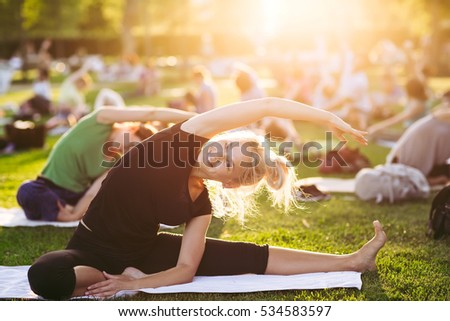 big group of adults attending a yoga class outside in park - Shutterstock ID 534583597