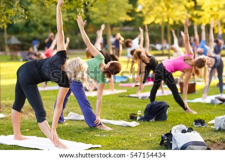 Shutterstock big group of adults attending a yoga class outside in park