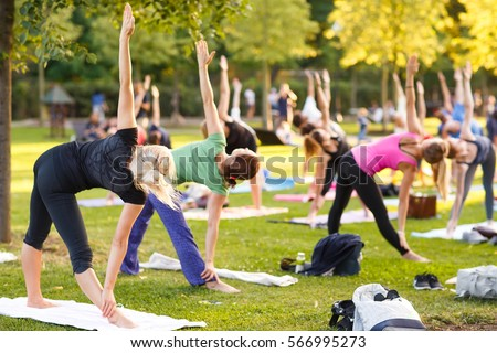 big group of adults attending a yoga class outside in park - Shutterstock ID 566995273