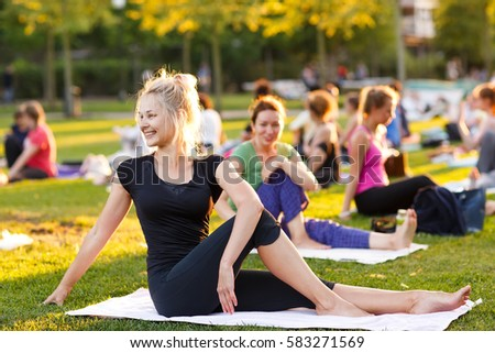 big group of adults attending a yoga class outside in park - Shutterstock ID 583271569
