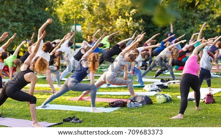 big group of adults attending a yoga class outside in park - Shutterstock ID 709683373