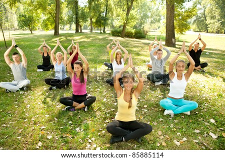 big group of adults attending a yoga class outside in park - stock photo