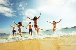 Big group of friends runs at sea beach. Tropical vacations concept