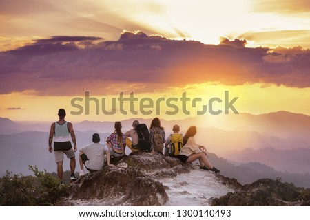 Big group of friends stands on mountain top and looks at beautiful sunset. Travel with friends concept #1300140493