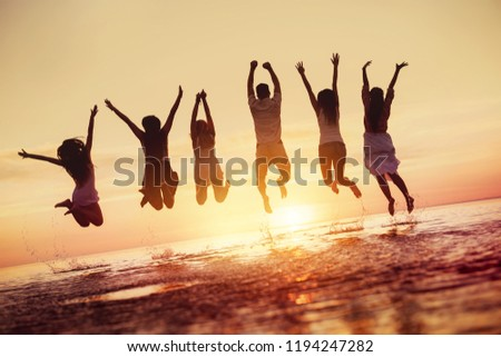 Big group of happy friends having fun and jumps in water against sunset #1194247282