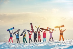 Big group of happy friends skiers and snowboarders having fun and holding ski and snowboards on mountain top