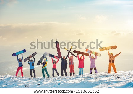 Big group of happy friends skiers and snowboarders having fun and holding ski and snowboards on mountain top #1513651352