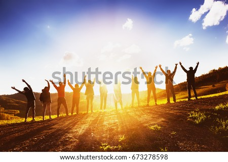 Big group of happy friends stands on sunset backdrop with raised arms together. Friendship or teamwork concept