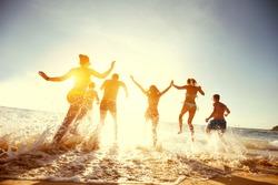 Big group of people having fun at sunset beach