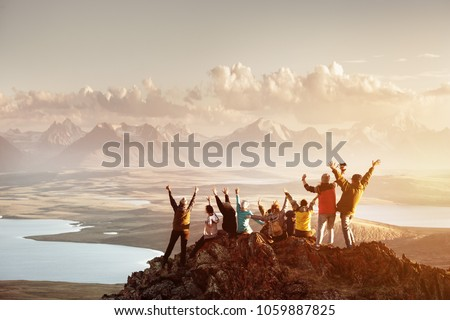Big group of people having fun in success pose with raised arms on mountain top against sunset lakes and mountains. Travel, adventure or expedition concept
