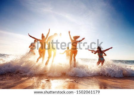 Big group of seven happy friends is having fun and runs at sunset beach to sun light and waves
