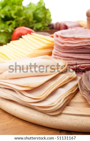 big group of sliced meat, cheese and vegetables