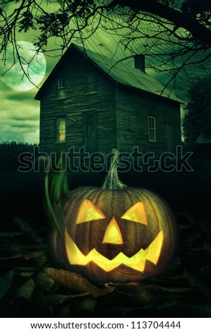 Big Halloween pumpkin in front of a Spooky house