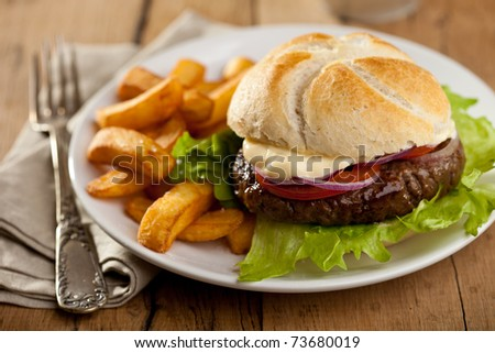 Big hamburger with onions, tomatoes and french fries