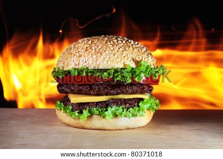 big hamburger with real fire on a background - stock photo