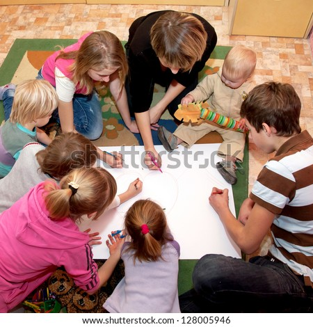 Big happy family - a mother and seven children drawing a heart together at home. Family concept.