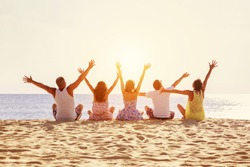 Big happy family or group of five friends is having fun against sunset beach. Beach holidays concept