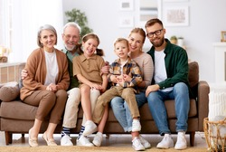 Big happy family. Portrait of grandparents, mother, father and two their cute kids, sister and brother, sitting together on coach at home and smiling at camera. Mortgage loan and real estate concept
