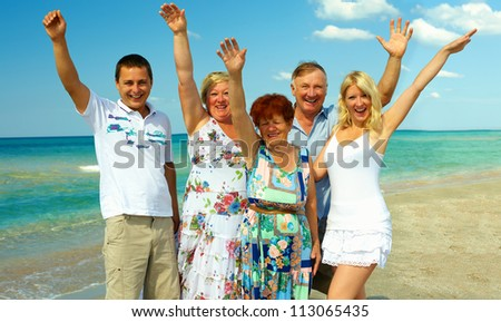 big happy family waving hands on sea beach