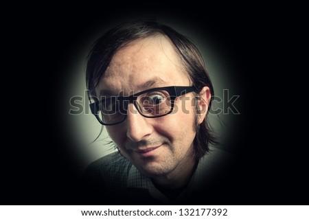 Big head nerd male  looking through the peephole, humorous concept photo.