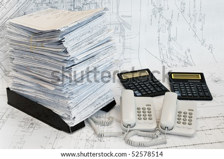 Big heap of design and project drawings, two calculators and two telephones on the table surface. White whatman are background.