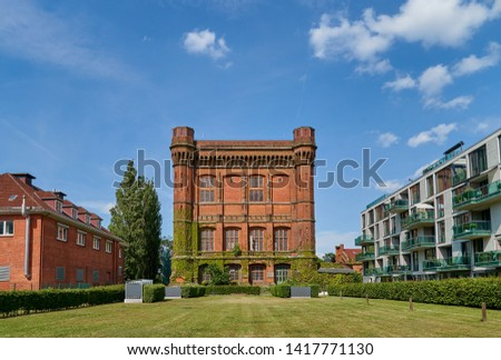 "big historic watertower building, officially ""watertower on the Werder"", popularly called ""the upturned chest of drawers"" in Bremen (Germany), completed in 1873 on a sunny summer day with blue sky"
